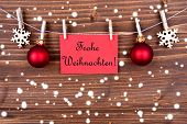 pic of weihnachten  - Red Label in the Snow Hanging on a Line with the German Words Frohe Weihnachten which means Merry Christmas