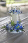 stock photo of centerpiece  - Candle in glass centerpiece. Cute blue flowers and ribbons adorn the glass.
