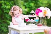 image of baby doll  - Adorable toddler girl with curly hair wearing a colorful dress on her birthday playing tea party with a teddy bear doll toy dishes cup cakes and muffins in a sunny summer garden - JPG