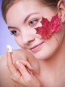 picture of capillary  - Face of young woman with leaf as symbol of red capillary skin on gray. Girl taking care of her dry complexion applying moisturizing cream. ** Note: Shallow depth of field - JPG