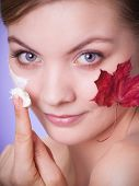 stock photo of capillary  - Face of young woman with leaf as symbol of red capillary skin on gray - JPG