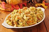 picture of cone  - A small casserole dish of cornbread stuffing on a rustic wooden table with autumn leaves and pine cones - JPG