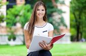 stock photo of bench  - Female student on a bench in a park - JPG