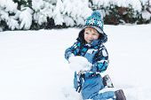 stock photo of snow forest  - Little toddler boy having fun with snow outdoors on beautiful winter day - JPG