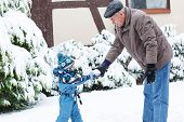 picture of grandfather  - Grandfather and granchild having fun with snow outdoors on beautiful winter day - JPG