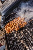 picture of peddlers  - cooking meat skewers on the grill in a thai food street market in bangkok - JPG