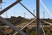 picture of tarifa  - Look through electricity pole to landscape with wind turbines - JPG