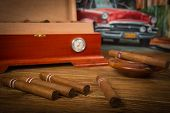 foto of ashes  - Cuban cigars and humidor with ashtray on rustic wooden table with Cuban painting of american old car in background - JPG