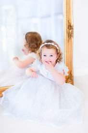 picture of toddlers tiaras  - Sweet curly little girl with big beautiful eyes iwearing a white bridesmaid dress sitting at a big window playing princess in a sunny living room - JPG