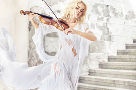 stock photo of hair motion  - Beautiful blond hair woman with violin - JPG