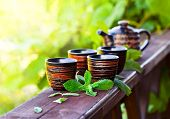 stock photo of teapot  - Teapot with small cups and peppermint leaves - JPG