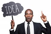 image of concentration man  - Surprised young African man in formalwear holding banner with text and pointing up while standing isolated on white background - JPG