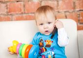 stock photo of toy phone  - little boy holding a phone and a bright toy - JPG