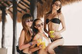 Постер, плакат: Three beautiful girls in a bar on the beach on the ocean