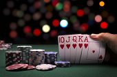 picture of poker hand  - A close up view of a poker hand and poker chips in a casino like setting - JPG