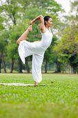 stock photo of natarajasana  - Beautiful woman practicing yoga in the park. Lord Shiva Dancing Pose Natarajasana. ** Note: Soft Focus at 100%, best at smaller sizes - JPG