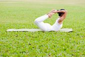 foto of dhanurasana  - Beautiful woman practicing yoga in the park - JPG