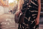 stock photo of buddhist  - A woman with a handbag is standing in the grounds of a buddhist temple - JPG
