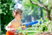 stock photo of kiddie  - Little blond child having fun with splashing water in summer garden playing water gun - JPG