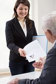 stock photo of presenter  - Young smiling woman presenting curriculum vitae on job interview - JPG