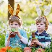 stock photo of bunny ears  - Family of two siblings: Little boys wearing Easter bunny ears at spring green grass and blooming apple garden eating chocolate bunny and having fun outdoors.