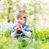 foto of bunny ears  - Funny child wearing Easter bunny ears at spring green grass and blooming apple garden eating chocolate bunny and having fun outdoors - JPG