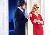 image of girl next door  - Attractive couple standing next to a white door - JPG