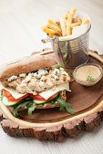 stock photo of cheese-steak  - Healthy wheat sandwich burger with BBQ grilled chicken steak cheese tomato rocket salad cucumber fried potato and mustard sauce served for eating on wooden board - JPG