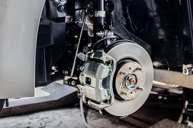 image of in front  - Front disc brake on car in process of new tire replacement - JPG