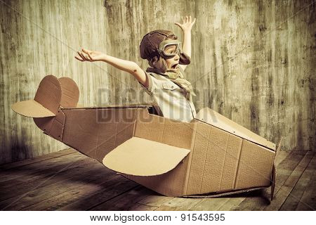 Cute visionary kid playing with a cardboard plane. Adolescence. Dream, creative energy. Retro style.