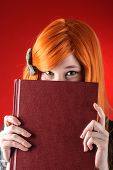 stock photo of peek  - Closeup of young redhead woman peeking over the edge of the closed book - JPG