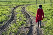 picture of country girl  - girl in red coat going far away by dirty country road selective focus on girl