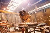 stock photo of protective eyewear  - Young man with protective goggles welding in a factory - JPG