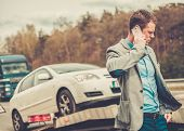 stock photo of pick up  - Man calling while tow truck picking up his broken car  - JPG