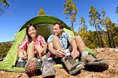 image of boot camp  - Camping people putting on hiking shoes by tent - JPG