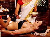 stock photo of panchakarma  - Woman having stomach ayurvedic massage with pouch of rice - JPG