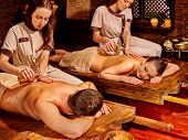 stock photo of ayurveda  - Couple  having oil Ayurveda spa treatment on exotic wooden bed - JPG