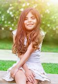 stock photo of daycare  - Portrait of a cute little girl sitting in the park and enjoying bright sunny day - JPG