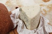 picture of deli  - aged italian deli fresh blue stilton cheese and rye ciabatta served on wooden cutting plate on used baking paper as background - JPG