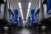 stock photo of passenger train  - Perspective view of seats from the aisle inside a passenger train - JPG