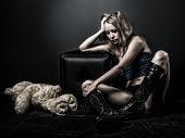 stock photo of saddening  - Beautiful teenager with blond hair in the style of anime in black army boots sitting on the dirty floor - JPG