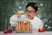 picture of chemical reaction  - Portrait of asian schoolboy playing chemical in laboratory with doodle on blackboard - JPG