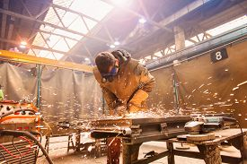 foto of welding  - Young man with protective goggles welding in a factory - JPG