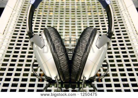 Picture or Photo of Symmetrical silver and black headphones on silver metal grid background