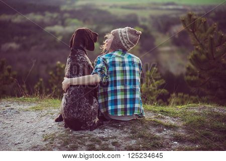 poster of Woman and her dog posing outdoor. Girl loving and hugging tightly her dog and watching landscape.