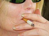 stock photo of smoking woman  - close-up of scarred woman smoking  - JPG