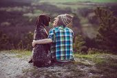 Woman and her dog posing outdoor. Girl loving and hugging tightly her dog and watching landscape. poster