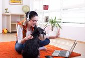 Girl With Dog Using Video Call On Laptop poster