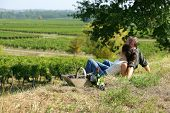stock photo of naturel  - Couple sat on the grass in front of vineyards - JPG