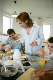 stock photo of matinee  - Portrait of a smiling family having breakfast - JPG